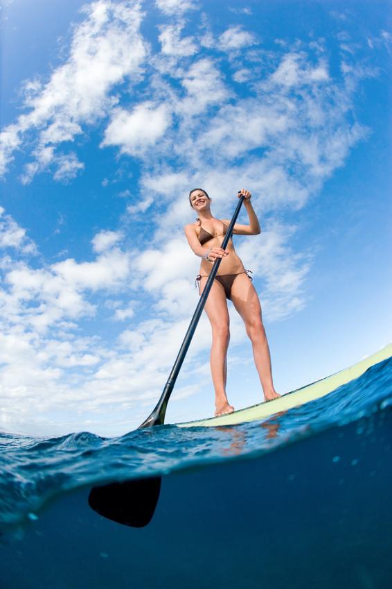 woman in bikini on paddleboard in blue ocean